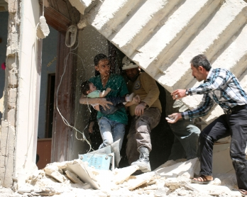 Syrians evacuate a toddler from a destroyed building following a reported air strike on the rebel-held neighbourhood of al-Kalasa in the northern Syrian city of Aleppo, on April 28, 2016. The death toll from an upsurge of fighting in Syria's second city A