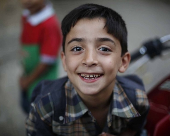A Syrian boy smiles at the camera in the city of Hamouria in Damascus province on the third day of Eid al-Adha celebrations on September 26, 2015.