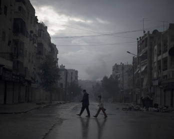 A father and son return home with vegetables, as smoke from a pro-government forces artillery strike ascends in the background, in the al-Amaria neighbourhoodin the city of Aleppo, on January 6, 2013.