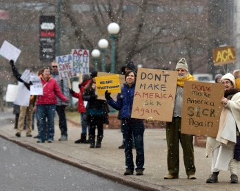 Demonstartors hold signs in the snow during a rally in support of the Affordable Care Act (ACA) in Denver, Colorado on January 15, 2017. - President-elect Donald Trump and his Republican allies have vowed a swift repeal of President Barack Obama's landmar