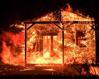 Flames overtake a structure as nearby homes burn in the Napa wine region in California on October 9, 2017, as multiple wind-driven fires continue to whip through the region.  /