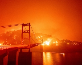 A boat motors by as the Bidwell Bar Bridge is surrounded by fire in Lake Oroville during the Bear fire in Oroville, California on September 9, 2020. - Dangerous dry winds whipped up California's record-breaking wildfires and ignited new blazes Tuesday, as