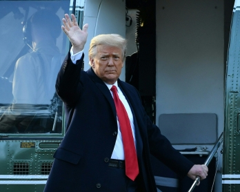Outgoing US President Donald Trump waves as he boards Marine One at the White House in Washington, DC, on January 20, 2021. - President Trump travels his Mar-a-Lago golf club residence in Palm Beach, Florida, and will not attend the inauguration for Presi