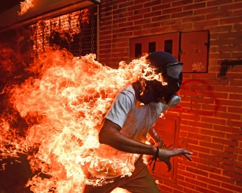 A demonstrator catches fire during clashes with riot police within a protest against Venezuelan President Nicolas Maduro, in Caracas on May 3, 2017.
