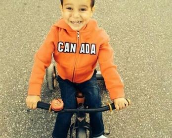 Le petit Abouzar Ahmad à Toronto le 12 mai 2014, moins de deux mois après avoir survécu miraculeusement au massacre de sa famille