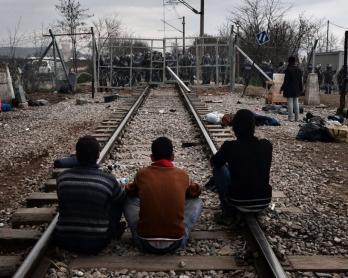 Des réfugiés attendent sur la voie ferrée reliant la Grèce à la Macédoine, devant la frontière bloquée par des policiers macédoniens, le 29 février 2016