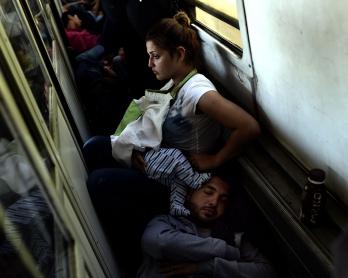 Alia et son bébé à bord d'un train en Macédoine, entre la frontière grecque et la frontière serbe, en août 2015