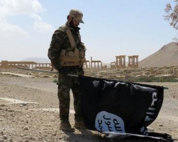 Un membre des forces pro-gouvernementales syriennes tient un drapeau du groupe Etat islamique découvert après la reconquête de Palmyre, le 27 mars 2016