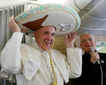 Le pape François essaye un chapeau offert par un journaliste mexicain dans l'avion entre Rome et La Havane, le 12 février 2016