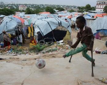 Un enfant somalien atteint de la polio joue au football dans le camp pour personnes déplacées de Sayyid à Mogadiscio le 12 juin 2014, le jour du coup d'envoi de la Coupe du monde au Brésil