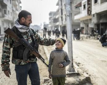 Un combattant kurde et son fils dans Kobané libérée, le 28 janvier 2015