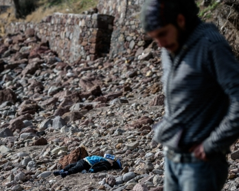 A man stands next to the body of a migrant child washed up on a beach in Canakkale's Bademli district on January 30, 2016