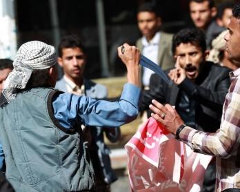 Un Houthi menace des manifestants yéménites opposés à la prise de contrôle de la capitale Sanaa par la rébellion chiite, le 24 janvier 2015
